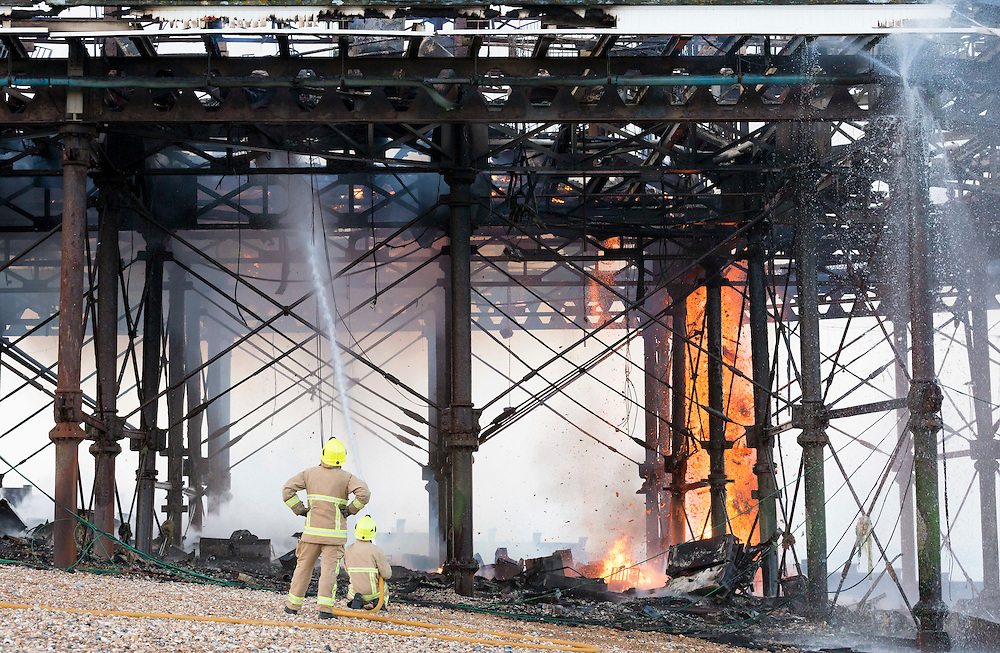 Fire fighters from East Sussex Fire and Rescue Service dampen down the flames following a large fire on the pier in Eastbourne, East Sussex. Picture date: Wednesday July 30, 2014. Photo credit should read: Chris Ison/Reuters