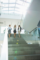 Happy businesswomen conversing while moving down steps in office