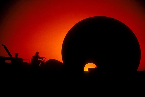 Silhouette of oil and gas pipe with worker at sunset.