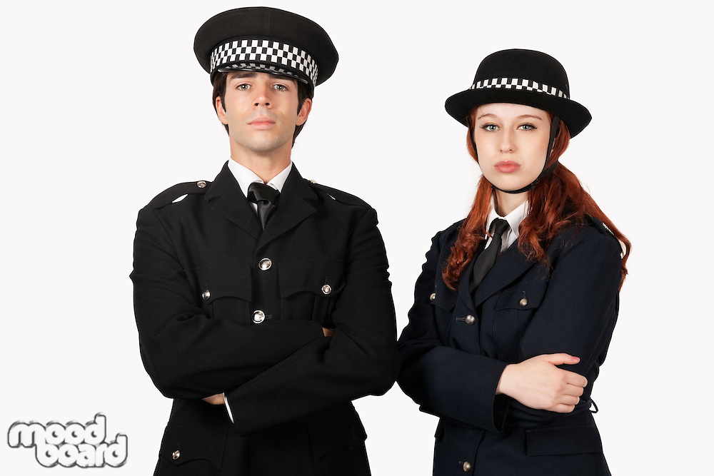 Portrait of confident police officers with arms crossed against white background