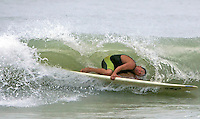 A surfer ducks under a wave as the surf continued to come up from Hurricane Wilma imminent arrival in Naples, Florida October 23, 2005. The storm is expected to make landfall Monday morning.