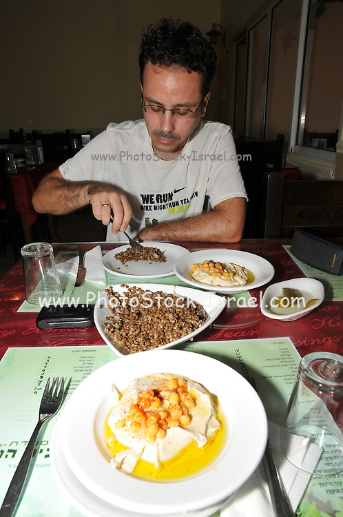 Man eats a serving of Humus, tahini and Olive oil