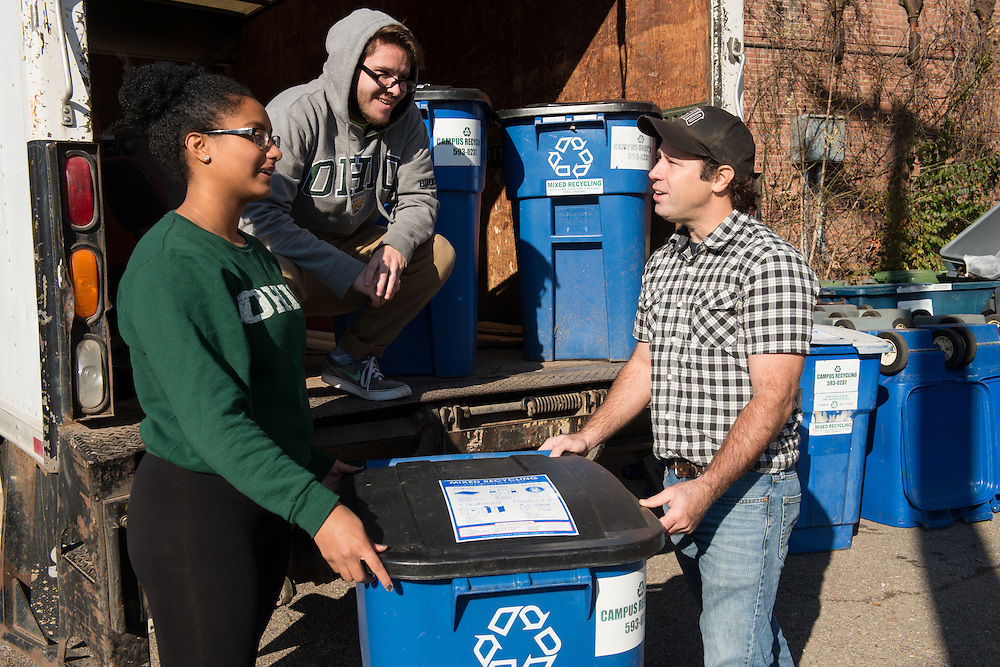 From left, Vanessa Thiel, Morgyn Freeland and Andrew Ladd transfer recycling containers at Ohio University's Campus Recycling center on November 15, 2016.