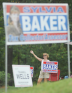 Sylvia Baker, candidate for tax assessor of Lafayette County, holds a sign as she campaigns outside the polls at the Chamber of Commerce in Oxford, Miss. on Tuesday, Aug. 23, 2011. Mississippians are going to the polls today to vote in primary runoffs in state and local elections. (AP Photo/Oxford Eagle, Bruce Newman)