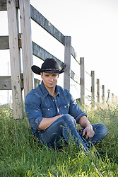 hot cowboy sitting by a rustic fence