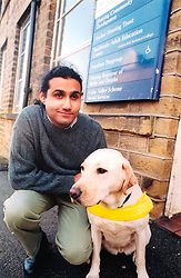 Visually impaired young man with his guide dog; UK