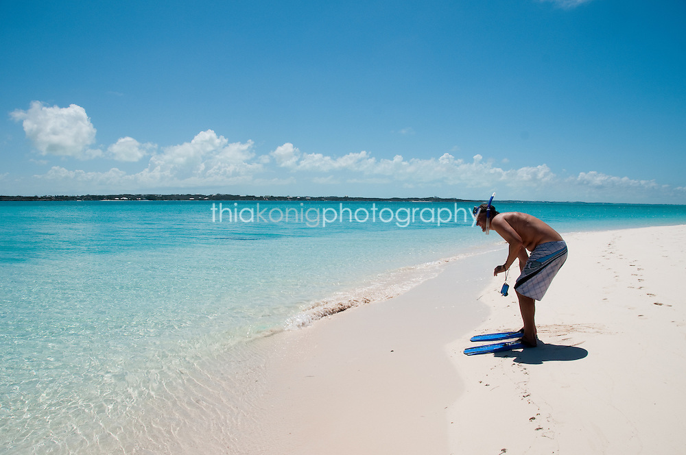 Quirky image of man with flippers getting ready to wade into aqua blue ocean, Bahamas.