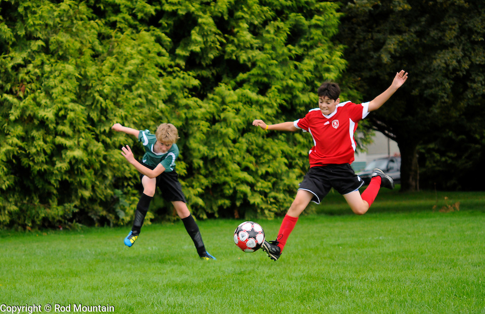 Two Boys are seen vying for the Soccer Ball during a match in Vancouver, British Columbia