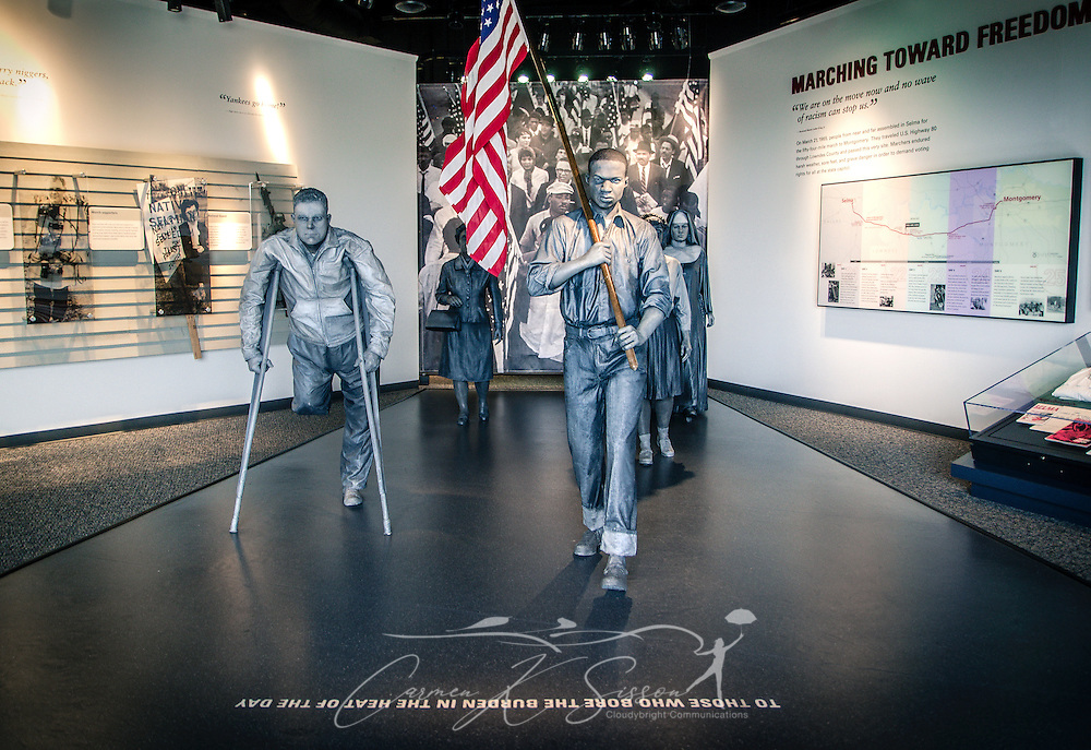 """An exhibit featuring the foot soldiers of the civil rights movement's Selma to Montomery march are displayed at Lowndes Interpretive Center, Feb. 3, 2015, in Hayneville, Ala. Dallas County Sheriff Jim Clark, Alabama state troopers, and newly deputized local citizens attacked the marchers as they tried to cross Selma's Edmund Pettus Bridge, March 7, 1965. More than 60 protesters were hospitalized due to their injuries, and the day became known as """"Bloody Sunday."""" The violent confrontation marked a pivotal turning point in the Civil Rights movement.  On March 21, 1965, activists crossed the Edmund Pettus Bridge and marched 54 miles to the Alabama State Capitol in Montgomery. The Voting Rights Act was passed, Aug. 6, 1965, outlawing poll taxes, literacy tests, and other methods used to prevent blacks from voting. The inscription on the floor reads: """"To those who bore the burden in the hea of  (Photo by Carmen K. Sisson/Cloudybright)"""