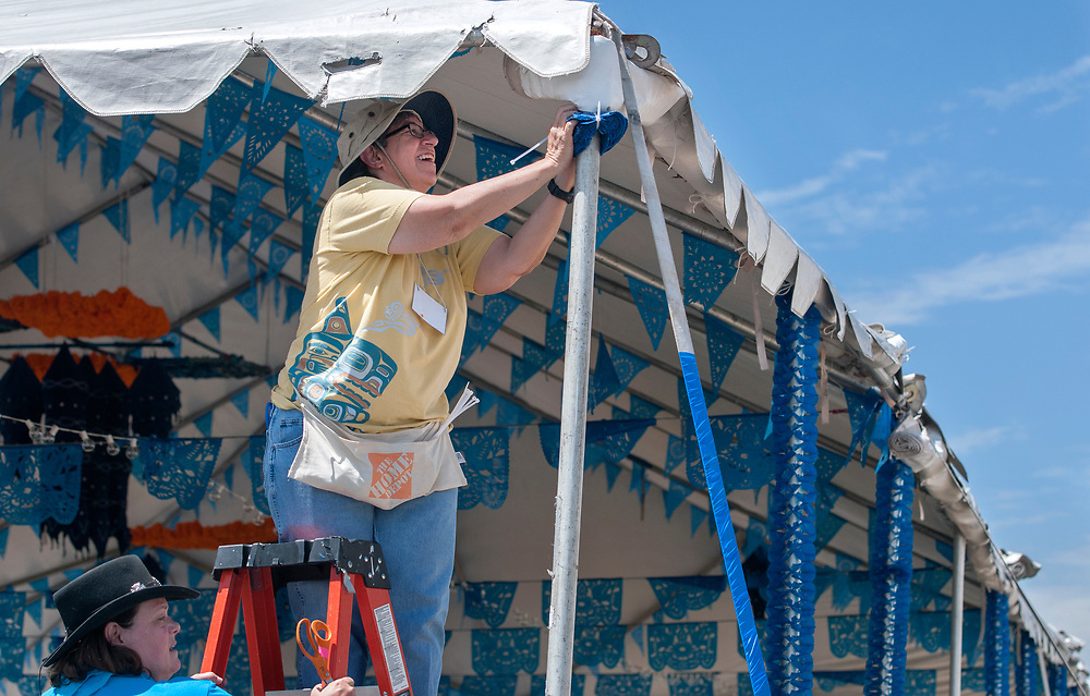 em071217c/b/Alison Brushaber, left, and Phyllis Roybal, both from Santa Fe, help decorate tents on Museum Hill in Santa Fe for the 2017 International Folf Art Marker. They were among around 2000 volunteers that are helping with the market this year. The event starts Thursday and runs through the weekend but the main public events are Saturday and Sunday with 160 artist from 53 countries. Photo shot Wednesday July 12, 2017.  (Eddie Moore/Albuquerque Journal)