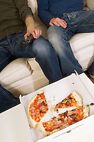 Half eaten pizza in box by people on sofa low section