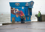 © Licensed to London News Pictures. 11/11/2014. Southsea, UK. A woman looks at the sea. Wet and windy weather today, 11 November 2014, at Southsea, Portsmouth. The Met Office have issued weather warnings in some parts of the UK. Photo credit : Stephen Simpson/LNP