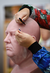 Sophie Crudgington inserts Yak hairs onto an unfinished wax figure of President-elect Donald Trump at the Madame Tussauds studio in west London, which will be released in January.