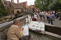 A sketch artist plys his trade as tourists takes in the sites next to the B&B Bonifacius (left) in Bruges, Belgium. (Photo © Jock Fistick)