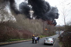 "© Licensed to London News Pictures . 15/03/2015 . Salford , UK . Roads are closed and people have been evacuated as a large fire burns at a unit within "" Junction Eco-Park "" in Clifton , Greater Manchester , this evening (Sunday 15th March 2015) . The smoke and flames can be seen for many miles . Forty fire fighters are at the scene working to control the blaze . Photo credit : Joel Goodman/LNP"