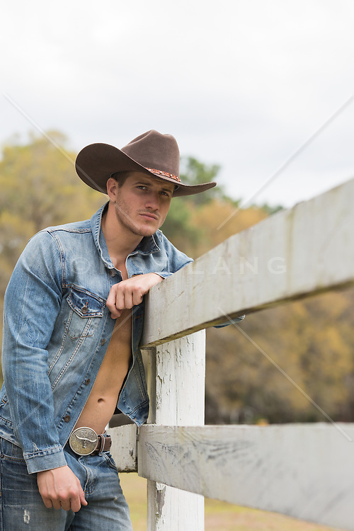 cowboy with an open denim shirt leaning on a wooden fence on a ranch