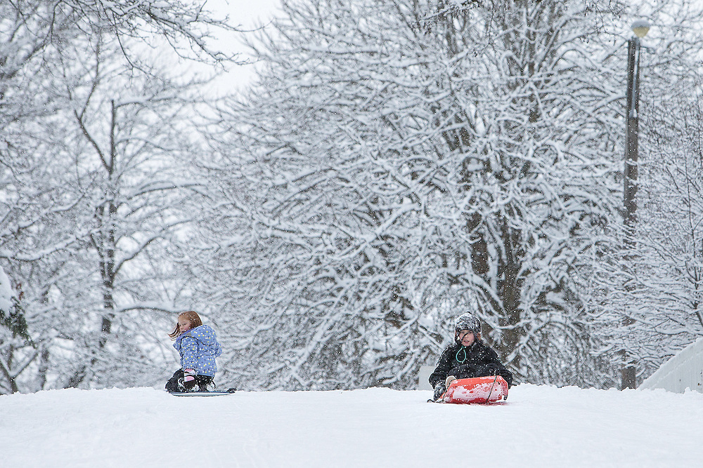 GABE GREEN/Press<br /> <br /> Sibling sledders Vaylynn, 6, left, and Vance Crawford, 9,  slide down a snowy hill on Boyd Avenue before dinner Thursday evening in Coeur d&rsquo;Alene.