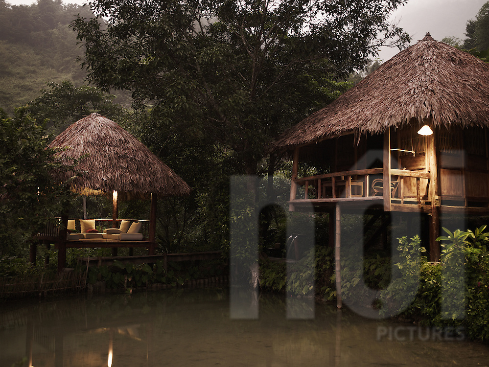 Two stilt houses at dawn nearby a pond in Hieu resort, Pu Luong natural reserve, Vietnam, Asia