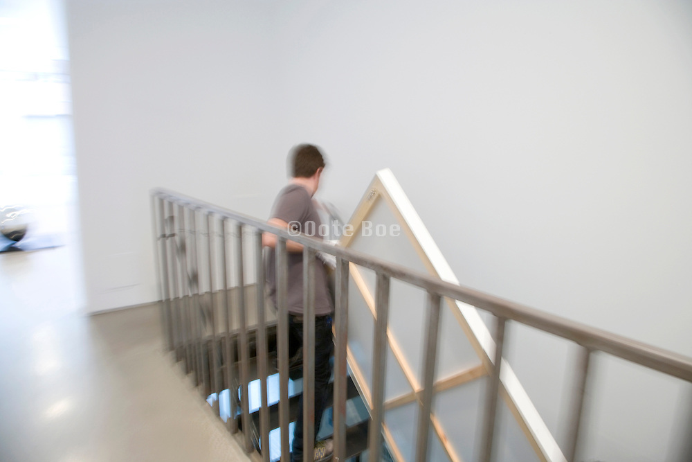 person carrying up the stars a large painting in a contemporary art gallery Chelsea New York