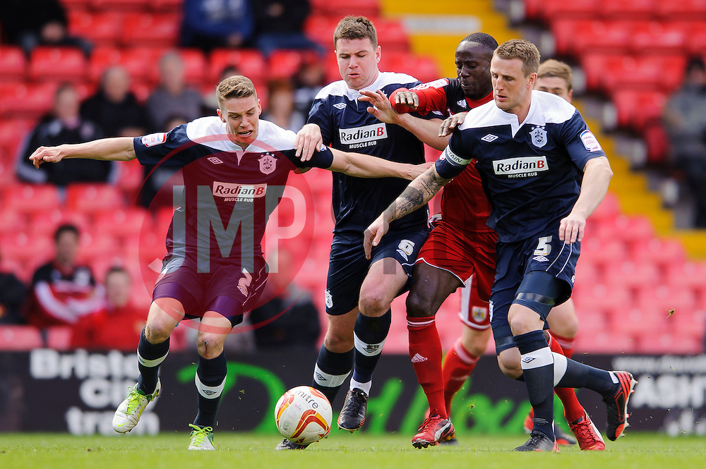 Bristol City Forward Albert Adomah (GHA) is surrounded by Huddersfield defenders including Huddersfield Defender Calum Woods (ENG) and Defender Peter Clarke (ENG) during the first half of the match - Photo mandatory by-line: Rogan Thomson/JMP - Tel: Mobile: 07966 386802 27/04/2013 - SPORT - FOOTBALL - Ashton Gate - Bristol. Bristol City v Huddersfield Town - npower Football League Championship.