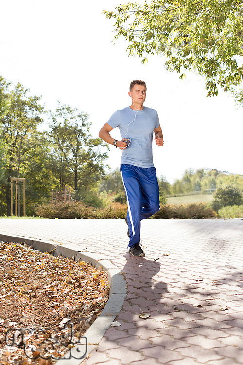 Full length of man listening music while jogging in park