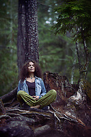 Young woman meditating in a forest sitting in meditation pose with her legs crossed leaning with her back against a tree in beautiful tranquil calm nature scenery