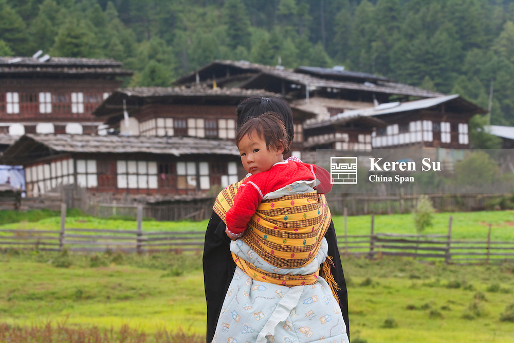 Woman carrying child on back with traditional houses, Phobjikha Valley, Bhutan