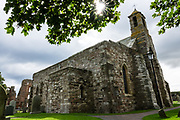 "The Anglican ""Parish Church of Saint Mary the Virgin"" dates from the 1100s-1200s, with major restoration in 1860, on the Holy Island of Lindisfarne, Northumberland, England, United Kingdom, Europe. Holy Island history dates from the 500s AD as an important center of Celtic Christianity under Saints Aidan of Lindisfarne, Cuthbert, Eadfrith of Lindisfarne, and Eadberht of Lindisfarne. After Viking invasions and the Norman conquest of England, a priory was reestablished. A small castle was built on Holy Island in 1550."