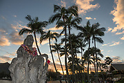 Statue with leis under palms at sunset, Nawiliwili Beach, island of Kauai, Hawaii, USA.