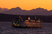 Sky over the Olympic Mountains glows orange at sunset seen from the Edmonds to Kingston Ferry, Washington, USA.