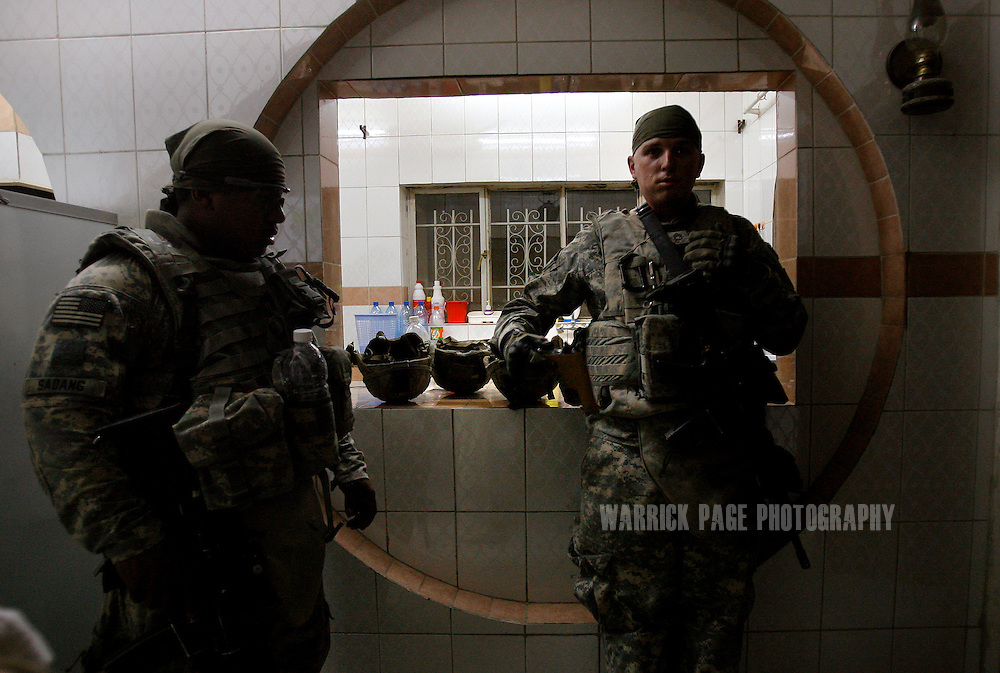 IRAQ, BAGHDAD - JUNE 25: SSgt. Kevin Skybrooks (31) (R) and Sgt. Staisman Sadang (L) with Alpha Company, 4th Battalion, 6th Armoured, 4th Brigade, 3rd Infantry Division stand in a civilian's kitchen after discovering a concealed weapon during a patrol in the suburb of Sadiyah, June 25, 2008 in Baghdad, Iraq. Neighbourhoods like Sadiyah became a battleground for Shiite militias and Sunni extremists after the bombing of the Golden Mosque in Samarra in 2006. Tens of thousands of people were either forced out of their homes or fled the violence to neigbouring countries or other parts of Iraq. Now predominantly Shiite, Sadiyah is being used as a test case by the Iraqi government to encourage the millions who have fled - many of which have the skills and money to rebuild the country. Since early 2008, Iraq's security situation has improved with oil production is increasing, record government surplus and easing sectarian tensions. (Photo by Warrick Page)
