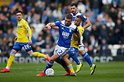 Birmingham City defender Harlee Dean  shields the ball from from Leeds United midfielder Kemar Roofe (7)  during the EFL Sky Bet Championship match between Birmingham City and Leeds United at St Andrews, Birmingham, England on 6 April 2019.