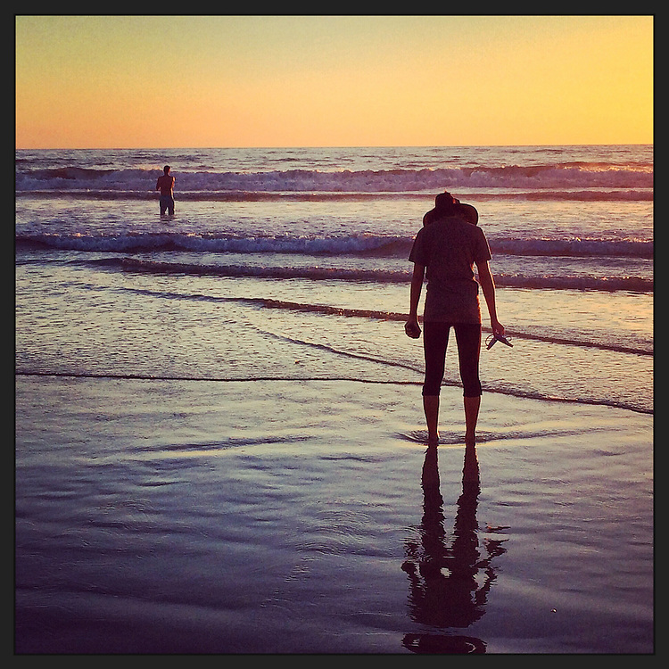 Woman holding her sandles checks her reflection in surf in Del Mar, CA