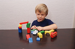 Young boy playing with toy car and coloured wooden lego,
