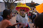 A man dressed as La Catrina, a traditional mexican skeletal figure by satyrical cartoonist José Guadalupe Posada representing Mexicans who aspire to live a euro-centric lifestyle, entertains attendees during the 2014 Mexican Network of Mining-Affected Peoples (REMA, for its initials in Spanish) Encounter. Hundreds of people from mining-affected communities throughout Mexico gathered for three days to exchange experiences, renew alliances and discuss strategies. Tlamanca, Zautla, Puebla, México. March 15, 2014.
