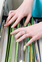 Teenaged girl on work experience placement from school doing some filing in the work place,