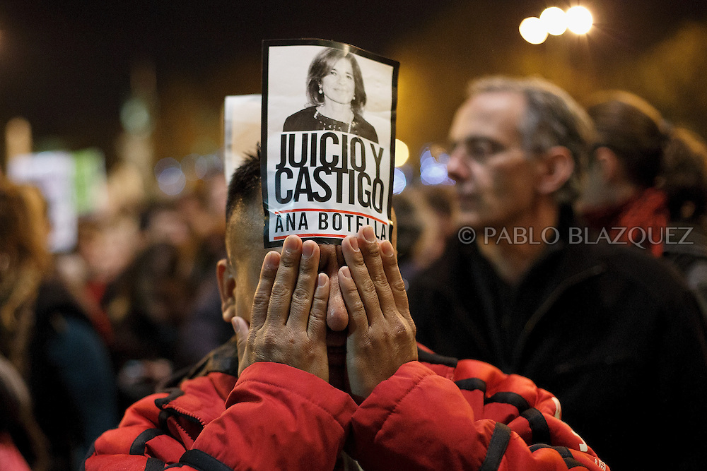 A man scratches his face as he wear a sticker reading 'Trial and Punishment. Ana Botella.' during a 'Surrounding the Congress' protest at Neptuno Square on December 14, 2013 in Madrid, Spain. Social movements groups called a 'Rodea el Congreso' 'Surrounding the Parliament' protest in reaction to the financial and social cuts, but also a new law the Spanish government is working that aims to set heavy fines. Around 1,500 policemen were on duty to protect the congress. The bill will set up fines of up to 30,000 euros for offenses related to social movements protests, insulting the state or offending or filming the authorities. After the demonstration some protesters clashed with riot policemen