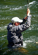 A fly fisherman fights a fish in the Taylor River in the Colorado Rocky Mountains