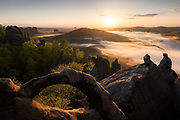 Blick über das Elbsandsteingebirge im Frühling mit Sonnenuntergang und Nebel über dem Kirnitzschtal, Schrammsteine, Falkenstein und Lilienstein im Hintergrund, Nationalpark Sächsische Schweiz, Sachsen, Deutschland * Wide view over the Elbe Sandstone Mountains in springtime with sunset and fog over the Kirnitzschtal, Schrammsteine, Falkenstein and Lilienstein in the background, Saxon Switzerland National Park, Saxony, Germany