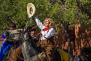 30 JUNE 2012 - PRESCOTT, AZ:  A woman on horseback waves to the crowd at the Prescott Frontier Days Rodeo Parade. The parade is marking its 125th year. It is one of the largest 4th of July Parades in Arizona. Prescott, about 100 miles north of Phoenix, was the first territorial capital of Arizona.    PHOTO BY JACK KURTZ