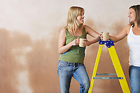 Two women leaning on step ladder holding mugs