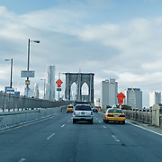 Driving on Brooklyn Bridge with yellow cabs.