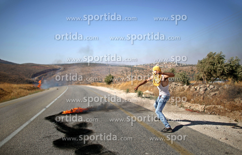 08.08.2015, Duma, PSE, Nahostkonflikt zwischen Israel und Pal&auml;stina, im Bild Ausschreitungen zwischen Israelischen Sicherheitskr&auml;fte und Pal&auml;stinensischen Autonomen // A Palestinian protester throws stones towards Israeli security forces during clashes on a street leading to Duma village, in a demonstration following the funeral of Saad Dawabsha, the father of a Palestinian toddler killed last week when their home was firebombed by Jewish extremists, near the West Bank city of Nablus. Dawabsha succumbed in hospital in the southern Israeli city of Beersheba where he was being treated for third degree burns while his wife Riham and four-year-old son Ahmed are still fighting for their lives, Palestine on 2015/08/08. EXPA Pictures &copy; 2015, PhotoCredit: EXPA/ APAimages/ Ahmad Talat<br /> <br /> *****ATTENTION - for AUT, GER, SUI, ITA, POL, CRO, SRB only*****