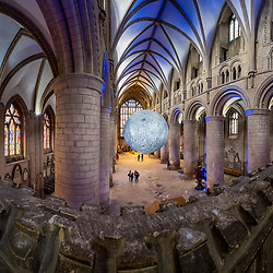 "© Licensed to London News Pictures 16/10/2019, Gloucester, UK. First day of ""The Museum of the Moon"" a touring artwork by artist Luke Jerram, displaying a 3D replica of the Moon, internally lit and floating in the Nave of Gloucester Cathedral. The lunar imagery is accompanied by immersive surround sound composed by BAFTA award winner, Dan Jones. This photohgraoh is a composite of 5 shots stitched to gether to make the final panorama. Photo Credit : Stephen Shepherd/LNP"