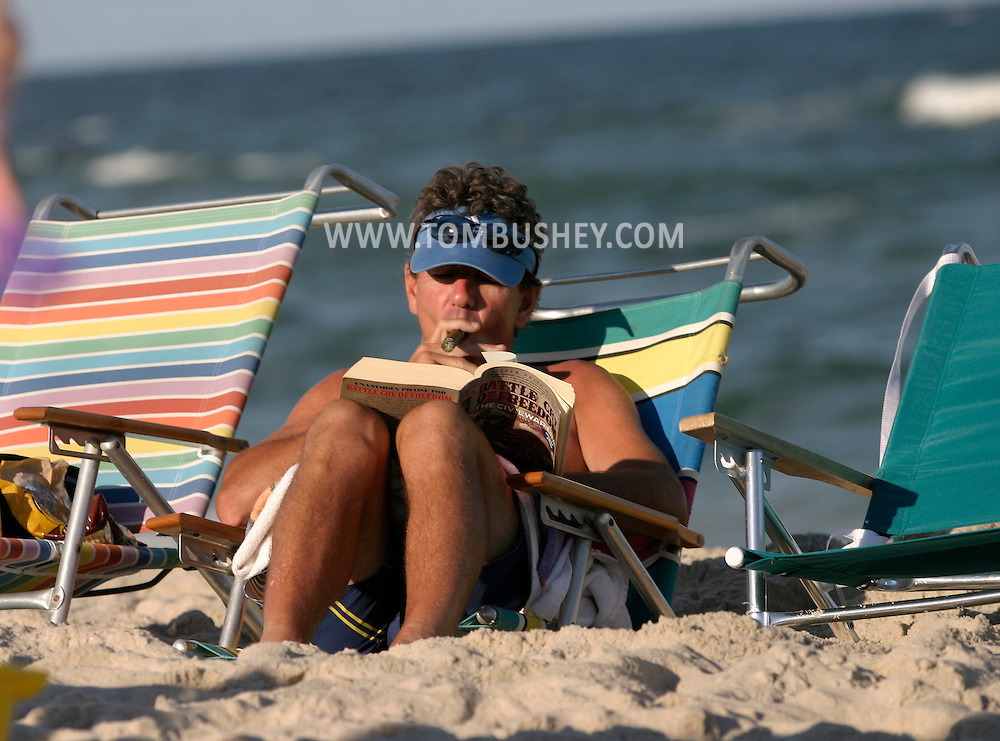 A man smokes a cigar while reading on the beach at Spray Beach on Long Beach Island, N.J..Aug. 25, 2005........