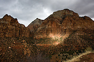 A sunbeam breaks through the cloud cover, casting a dramatic light across the rock wall, Zion National Park
