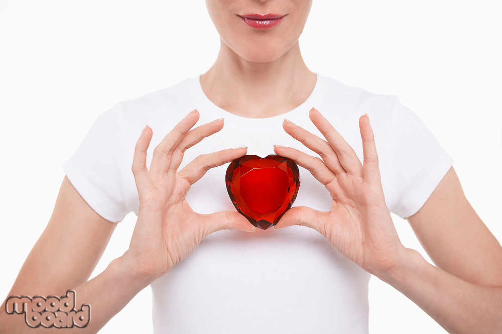 Woman in white t-shirt holding red glass heart in both hands