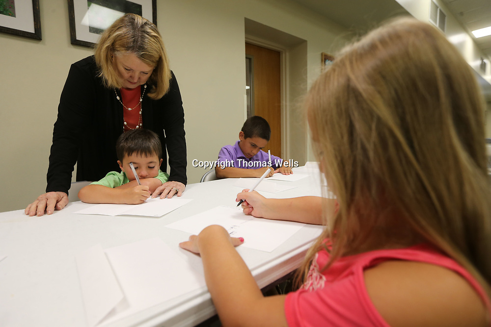 Mary Elizabeth Williams helps Cameron Howell write a thank you letter during an etiquette class at First Presbyterian Church in Tupelo.