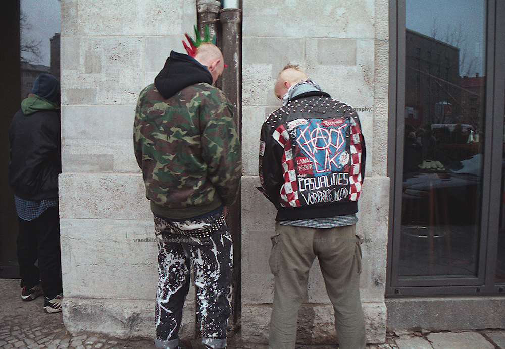 Punker urinieren in Berlin an eine Hauswand. Punks piss to a Wall in Berlin.
