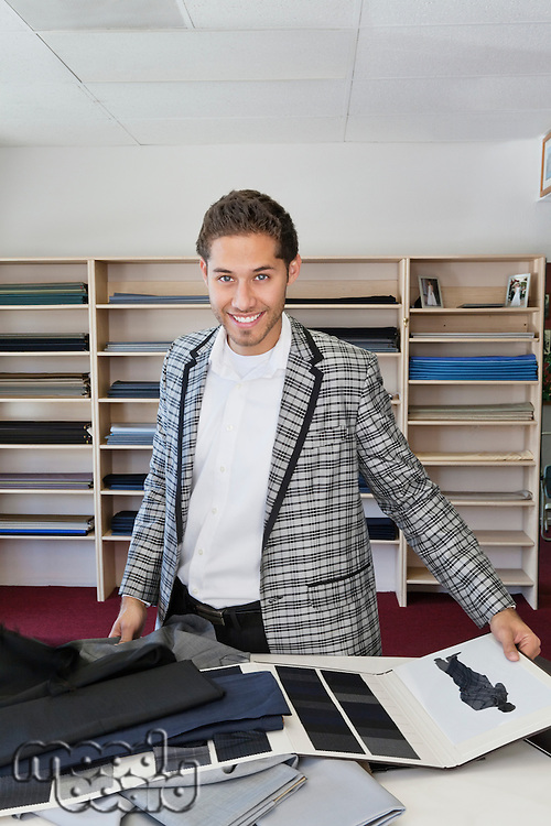Portrait of handsome young man choosing fabric for making suit in tailor's shop